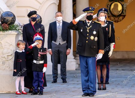Prince Albert II of Monaco (R) and Prince Jacques of Monaco (3L) salute next to Princess Charlene of Monaco (2L) and Princess Gabriella of Monaco attend the celebrations marking Monaco's National Day at the Palace in Monaco