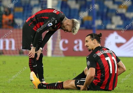 AC Milan's Swedish forward Zlatan Ibrahimovic lies on the ground next to teammate AC Milan's French defender Theo Hernandez after suffering an injury during the Serie A football match SSC Napoli vs AC Milan. AC Milan won 3-1.