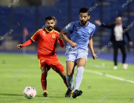 Stock Image of Al-Quadisiya's player Hassan Al-Amri (L) in action against Al-Batin's Renato Chaves (R) during the Saudi Professional League soccer match between Al-Quadisiya and Al-Batin at Prince Mohammed Bin Fahd Stadium, in Dammam, Saudi Arabia, 23 November 2020.