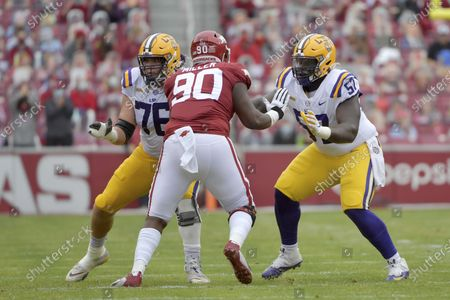 Linemen Austin Deculus (76) and Chasen Hines (57) block Arkansas defender Marcus Miller (90) during the first half of an NCAA college football game, in Fayetteville, Ark