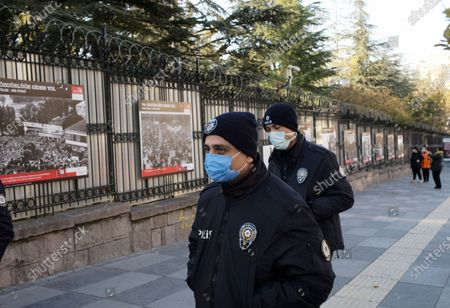Turkish police officers wearing masks to help protect against the spread of coronavirus, patrol during the opening of an open air photo exhibition about Lech Walesa, Polish statesman, dissident, and Nobel Peace Prize laureate, who served as the first democratically elected president of Poland from 1990 to 1995, and his Solidarity movement, in Ankara, Turkey, . Turkey's daily coronavirus deaths hit a record high as a series of restrictions aiming to slow the surge of COVID-19 infections came into effect
