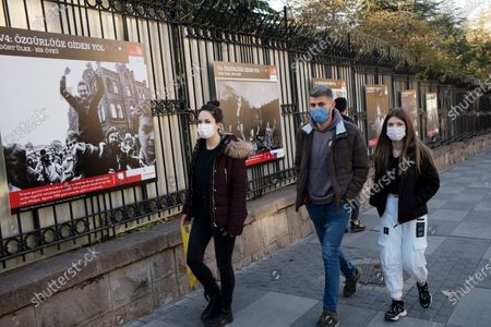 People wearing masks to help protect against the spread of coronavirus, speak during the opening of an open air photo exhibition about Lech Walesa, Polish statesman, dissident, and Nobel Peace Prize laureate, who served as the first democratically elected president of Poland from 1990 to 1995, and his Solidarity movement, in Ankara, Turkey, . Turkey's daily coronavirus deaths hit a record high as a series of restrictions aiming to slow the surge of COVID-19 infections came into effect