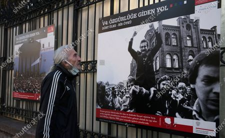 Man wearing a mask to help protect against the spread of coronavirus, visits an open air photo exhibition about Lech Walesa, Polish statesman, dissident, and Nobel Peace Prize laureate, who served as the first democratically elected president of Poland from 1990 to 1995, and his Solidarity movement, in Ankara, Turkey, . Turkey's daily coronavirus deaths hit a record high as a series of restrictions aiming to slow the surge of COVID-19 infections came into effect