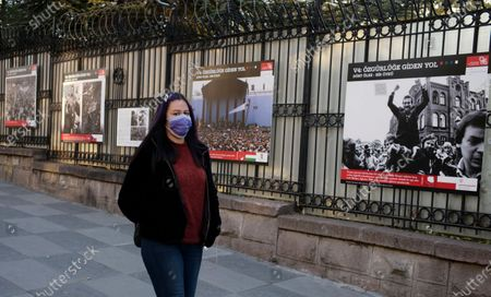 Woman wearing a mask to help protect against the spread of coronavirus, walks past an open air photo exhibition about Lech Walesa, Polish statesman, dissident, and Nobel Peace Prize laureate, who served as the first democratically elected president of Poland from 1990 to 1995, and his Solidarity movement, in Ankara, Turkey, . Turkey's daily coronavirus deaths hit a record high as a series of restrictions aiming to slow the surge of COVID-19 infections came into effect