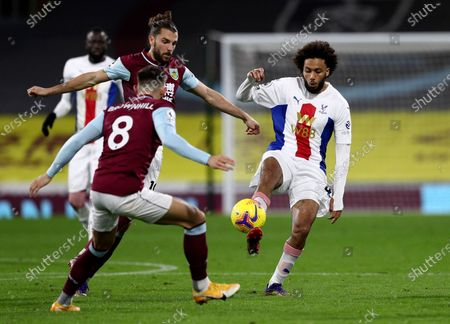 Crystal Palace's Jairo Riedewald, right, duels for the ball with Burnley's Jay Rodriguez and Burnley's Josh Brownhill during the English Premier League soccer match between Burnley and Crystal Palace at the Turf Moor stadium in Burnley, England