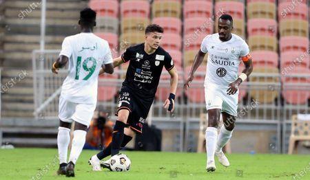 Al-Ahli's players Samuel Owusu (L) and Motaz Hawsawi (R) in action against Al-Shabab's Abdullah Alhamddan (C) during the Saudi Professional League soccer match between Al-Ahli and Al-Shabab at King Abdullah Sport City Stadium, 30 kilometers north of Jeddah, Saudi Arabia, 23 November 2020.