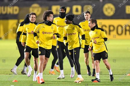 Stock Picture of Dortmund's Youssoufa Moukoko, 3rd from right, exercises with Dortmund's Axel Witsel, 2nd from left, during a training session prior the Champions League group F soccer match between Borussia Dortmund and Club Brugge in Dortmund, Germany, . The 16-year old forward Youssoufa Moukoko could become the youngest player ever in the Champions League on Tuesday