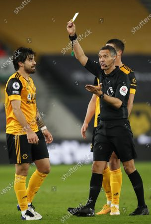 Ruben Neves (L) of Wolverhampton is shown the yellow card by referee Andre Marriner (R) during the English Premier League soccer match between Wolverhampton Wanderers and Southampton FC in Wolverhampton, Britain, 23 November 2020.
