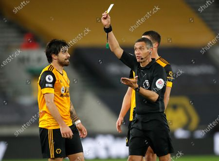 Referee Andre Marriner shows Wolverhampton Wanderers' Ruben Neves a yellow card during the English Premier League soccer match between Wolverhampton Wanderers and Southampton at Molineux Stadium in Wolverhampton, England