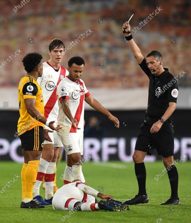 Referee Andre Marriner show s yellow card to Wolverhampton Wanderers' Adama Traore, left, during the English Premier League soccer match between Wolverhampton Wanderers and Southampton at Molineux Stadium in Wolverhampton, England