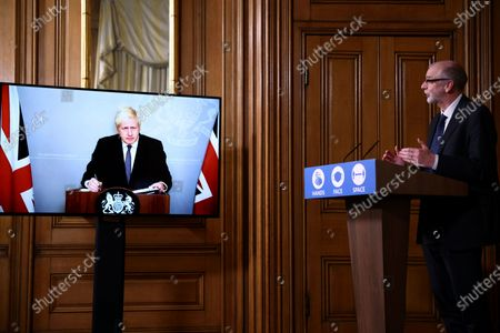 Britain's Prime Minister Boris Johnson appears on screen during a coronavirus news conference with Director of the Oxford Vaccine Group Andrew Pollard, right, giving an update about COVID-19 pandemic, at Downing Street in London, . Johnson is in quarantine after he came into contact with a confirmed coronavirus sufferer