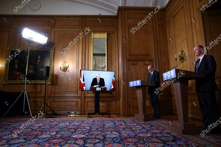Britain's Prime Minister Boris Johnson appears on screen during a coronavirus news conference with Chief Medical Officer for England Chris Whitty, right, and Director of the Oxford Vaccine Group Andrew Pollard giving an update about COVID-19 pandemic, at Downing Street in London, . Johnson is in quarantine after he came into contact with a confirmed coronavirus sufferer