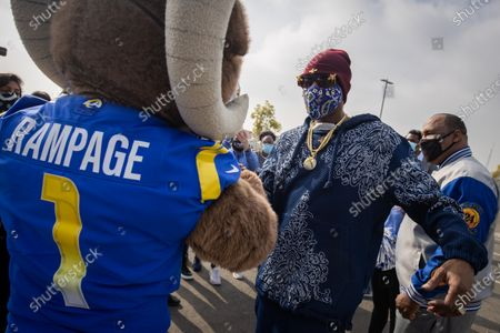 US rapper Snoop Dogg greets the LA Rams mascot, Rampage, at a drive-thru Thanksgiving meal distribution in front of SoFi Stadium in Inglewood, California, USA, 23 November 2020. Some 2,500 families from Inglewood picked up free thanksgiving meals at a drive-thru in front of SoFi Stadium.