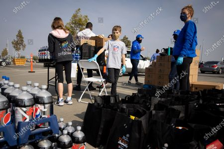 Volunteers wait to give out food at a drive-thru Thanksgiving meal distribution in front of SoFi Stadium in Inglewood, California, USA, 23 November 2020. Some 2,500 families from Inglewood picked up free thanksgiving meals at a drive-thru in front of SoFi Stadium.