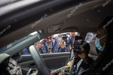 US rapper Snoop Dogg greets a family at a drive-thru Thanksgiving meal distribution in front of SoFi Stadium in Inglewood, California, USA, 23 November 2020. Some 2,500 families from Inglewood picked up free thanksgiving meals at a drive-thru in front of SoFi Stadium.