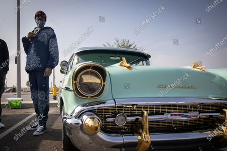 US rapper Snoop Dogg stands by his Chevrolet lowrider at a drive-thru Thanksgiving meal distribution in front of SoFi Stadium in Inglewood, California, USA, 23 November 2020. Some 2,500 families from Inglewood picked up free thanksgiving meals at a drive-thru in front of SoFi Stadium.