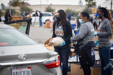 Volunteers give out food at a drive-thru Thanksgiving meal distribution in front of SoFi Stadium in Inglewood, California, USA, 23 November 2020. Some 2,500 families from Inglewood picked up free thanksgiving meals at a drive-thru in front of SoFi Stadium.