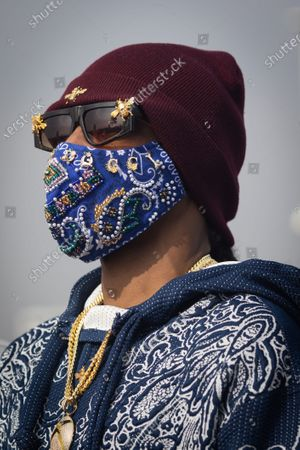 US rapper Snoop Dogg wears a mask with his name on it at a drive-thru Thanksgiving meal distribution in front of SoFi Stadium in Inglewood, California, USA, 23 November 2020. Some 2,500 families from Inglewood picked up free thanksgiving meals at a drive-thru in front of SoFi Stadium.