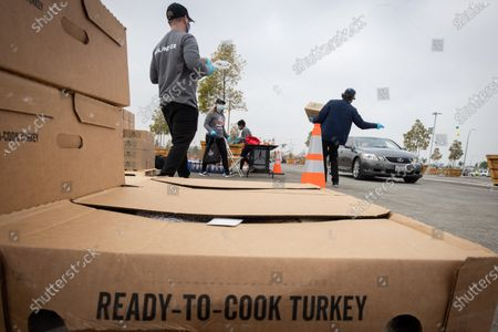 Volunteers give away turkeys and ingredients at a drive-thru Thanksgiving meal distribution in front of SoFi Stadium in Inglewood, California, USA, 23 November 2020. Some 2,500 families from Inglewood picked up free thanksgiving meals at a drive-thru in front of SoFi Stadium.