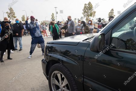 Stock Photo of US rapper Snoop Dogg greets a family at a drive-thru Thanksgiving meal distribution in front of SoFi Stadium in Inglewood, California, USA, 23 November 2020. Some 2,500 families from Inglewood picked up free thanksgiving meals at a drive-thru in front of SoFi Stadium.