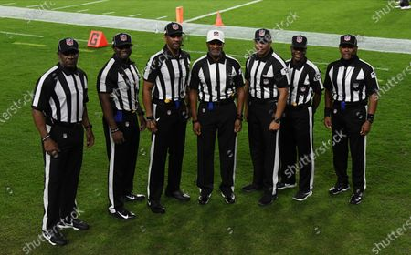Officials, from left, umpire Barry Anderson, side judge Anthony Jeffries, down judge Julian Mapp, referee Jerome Boger, back judge Greg Steed, field judge Dale Shaw (104), line judge Carl Johnson (101) pose for a photo before an NFL football game between the Tampa Bay Buccaneers and the Los Angeles Rams, in Tampa, Fla. The game is the first in NFL history to feature an all African-American officiating crew