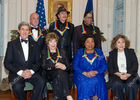 The five recipients of the 2013 Kennedy Center Honors pose for a group photo following a dinner hosted by United States Secretary of State John F. Kerry at the U.S. Department of State in Washington, D.C.. The 2013 honorees are opera singer Martina Arroyo; pianist, keyboardist, bandleader and composer Herbie Hancock; pianist, singer and songwriter Billy Joel; actress Shirley MacLaine; and musician and songwriter Carlos Santana. Seated in the front row are: U.S. Secretary of State John Kerry, Shirley MacLain, Martina Arroyo, and Teresa Heinz Kerry. Standing are Billy Joel, Carlos Santana, and Herbie Hancock.