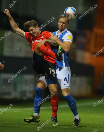James Collins of Luton Town clears the ball under pressure from Marc Roberts of Birmingham City