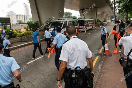 Stock Image of Police officers leave the West Kowloon Law Courts building premises after they cordon the area as Joshua Wong, Ivan Lam and Agnes Chow were expected to carried away by the Correctional Services vehicle on November 2020 in Hong Kong, China. The pro-democracy activists Joshua Wong, Ivan Lam and Agnes Chow were taken into custody after they pled guilty to inciting and organizing an unauthorized assembly related to last year protest.
