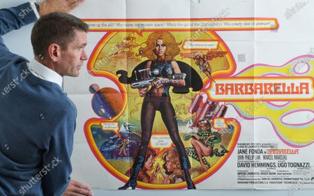 A poster for 1968 Sci-fi  Barbarella starring Jane Fonda which sold for £1,200. Auctioneer Neil Shuttleworth gets the poster ready for sale.  A retired film projectionist has sold hundreds of movie posters he saved from the bin for £34,000.  The unnamed vendor worked for a film company that showed new releases in town and village halls in rural Somerset during the 1970s and '80s.  For every movie he was sent one or two advertising posters to pin up outside the venues.
