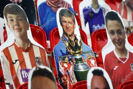 Ex Arsenal Manager Arsene Wenger is seen with the Premier League trophy as a cardboard cut out in the stand.
