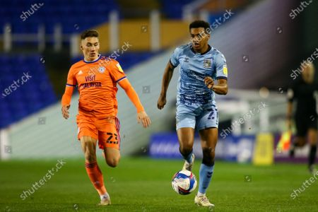 Sam McCallum #21 of Coventry City dribbles the ball under pressure from Harry Wilson #23 of Cardiff City