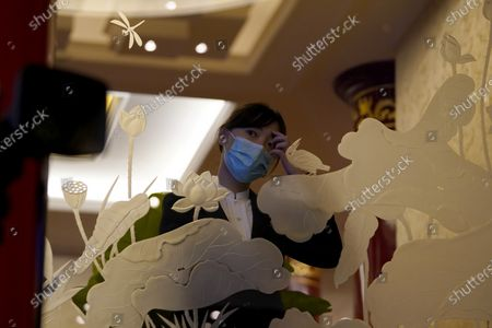"Worker wearing a mask to protect herself from the coronavirus wait for the start of a video conference session held by Chinese Premier Li Keqiang for the Fifth ""1+6"" Round Table Dialogue at the Diaoyutai state guesthouse in Beijing on . Premier Li is holding the roundtable session on promoting World Economic Recovery and Growth in the Post-COVID-19 era with leaders from international institutions including the World Bank and International Monetary Fund"