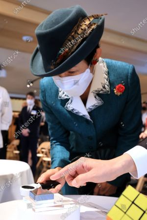 """Japanese Princess Takamado admires a 9.9mm cubu allow made Lubik's Cube witha magnifier at a reception for the 40th anniversary of Lubik's Cube puzzle in Tokyo on Tuesday, November 24, 2020. Japanese artists produced art works for the anniversary of Lubik's Cube """"Lubik's Cube Inspiration Project"""" and the embassy will have auction for charity."""