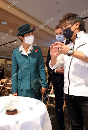 """Stock Picture of Japanese Princess Takamado (L) listens to patissier Susumu Koyama (R) as he shows a chocollate made Lubik's Cubesmiles at a reception for the 40th anniversary of Lubik's Cube puzzle in Tokyo on Tuesday, November 24, 2020. Japanese artists produced art works for the anniversary of Lubik's Cube """"Lubik's Cube Inspiration Project"""" and the embassy will have auction for charity."""