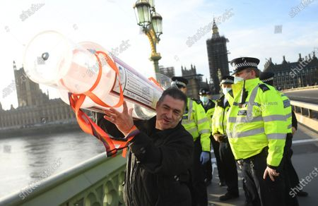 An anti-vax demonstrator talks to police while carrying a large syringe after protesting against Covid-19 vaccination, outside the headquarters of the Bill and Melinda Gates Foundation in London, Britain, 24 November 2020. Vaccine trials from a number of pharmaceutical companies are proving successful, giving hope at ending restrictions due to the ongoing coronavirus pandemic.