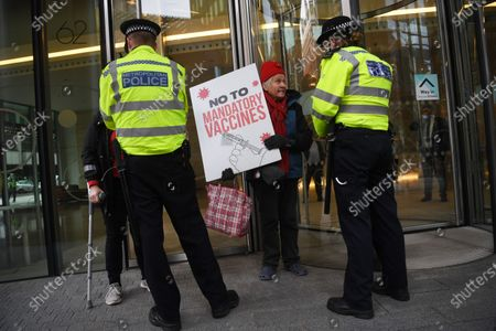 An anti-vax demonstrator talks to police while protesting against Covid-19 vaccination, outside the headquarters of the Bill and Melinda Gates Foundation in London, Britain, 24 November 2020. Vaccine trials from a number of pharmaceutical companies are proving successful, giving hope at ending restrictions due to the ongoing coronavirus pandemic.