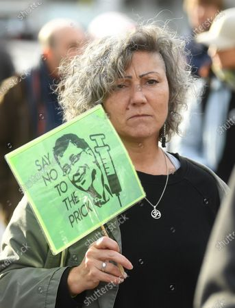 A woman holds a placard after protesting against Covid-19 vaccination, outside the headquarters of the Bill and Melinda Gates Foundation in London, Britain, 24 November 2020. Vaccine trials from a number of pharmaceutical companies are proving successful, giving hope at ending restrictions due to the ongoing coronavirus pandemic.