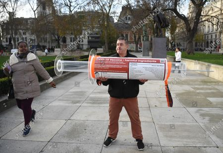 A man holds an oversized syringe after protesting against Covid-19 vaccination, outside the headquarters of the Bill and Melinda Gates Foundation in London, Britain, 24 November 2020. Vaccine trials from a number of pharmaceutical companies are proving successful, giving hope at ending restrictions due to the ongoing coronavirus pandemic.