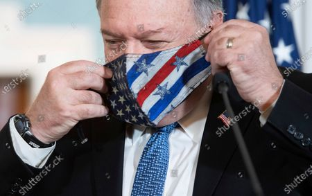 Secretary of State Mike Pompeo puts on his mask after speaking to the media prior to meeting with Kuwaiti Foreign Minister Sheikh Ahmad Nasser Al-Mohammad Al-Sabah at the State Department, in Washington