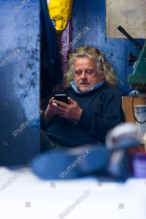 Paul King, a shoesmith in Tunbridge Wells, checks his phone between customers with one week of lockdown to go.