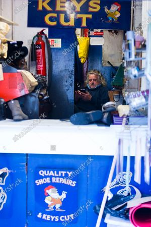 Stock Image of Paul King, a shoesmith in Tunbridge Wells, checks his phone between customers with one week of lockdown to go.