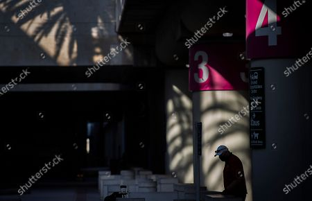 A traveler is silhouetted by the afternoon sun and shadows at John Wayne Airport for Thanksgiving holiday getaway Monday, Nov. 23, 2020 in Santa Ana. Millions of Americans are carrying on with their travel plans ahead of Thanksgiving weekend despite the CDC's urgent warnings to stay home as the number of daily cases and hospitalizations in the country continue to hit record highs. Confirmed cases in the U.S. for the disease topped 12 million on Saturday as more than 193,000 new infections were recorded in the US on Friday. This broke the previous record for the largest single-day spike on Thursday - and over 82,000 patients are now hospitalized across the country. (Allen J. Schaben / Los Angeles Times)