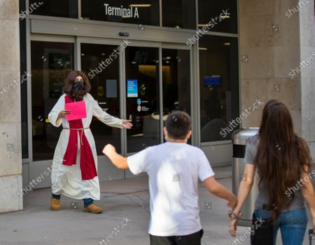 David Dawud, left, of Corona, surprises his cousin, Hanna Jimenez, right, of Lawton, Oklahoma, by wearing a Jesus costume as she arrives at John Wayne Airport for Thanksgiving holiday Monday, Nov. 23, 2020 in Santa Ana. Millions of Americans are carrying on with their travel plans ahead of Thanksgiving weekend despite the CDC's urgent warnings to stay home as the number of daily cases and hospitalizations in the country continue to hit record highs. Confirmed cases in the U.S. for the disease topped 12 million on Saturday as more than 193,000 new infections were recorded in the US on Friday. This broke the previous record for the largest single-day spike on Thursday - and over 82,000 patients are now hospitalized across the country. (Allen J. Schaben / Los Angeles Times)