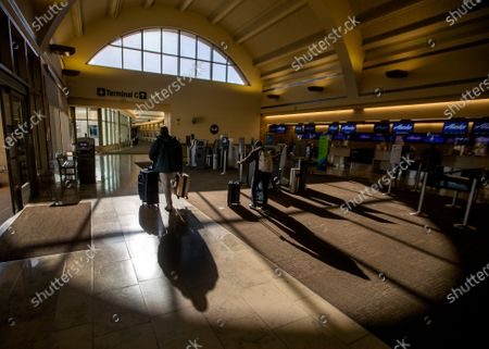 Travelers wearing masks are silhouetted by the afternoon sun as they make their way through the shadows at John Wayne Airport for Thanksgiving holiday getaway Monday, Nov. 23, 2020 in Santa Ana. Millions of Americans are carrying on with their travel plans ahead of Thanksgiving weekend despite the CDC's urgent warnings to stay home as the number of daily cases and hospitalizations in the country continue to hit record highs. Confirmed cases in the U.S. for the disease topped 12 million on Saturday as more than 193,000 new infections were recorded in the US on Friday. This broke the previous record for the largest single-day spike on Thursday - and over 82,000 patients are now hospitalized across the country. (Allen J. Schaben / Los Angeles Times)