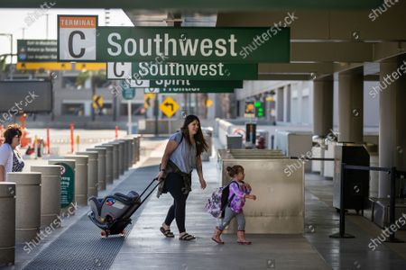 Travelers arrive at John Wayne Airport for Thanksgiving holiday getaway Monday, Nov. 23, 2020 in Santa Ana. Millions of Americans are carrying on with their travel plans ahead of Thanksgiving weekend despite the CDC's urgent warnings to stay home as the number of daily cases and hospitalizations in the country continue to hit record highs. Confirmed cases in the U.S. for the disease topped 12 million on Saturday as more than 193,000 new infections were recorded in the US on Friday. This broke the previous record for the largest single-day spike on Thursday - and over 82,000 patients are now hospitalized across the country. (Allen J. Schaben / Los Angeles Times)