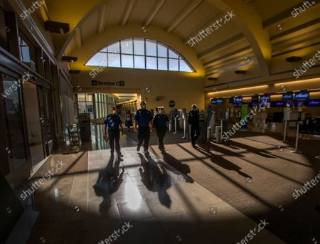 Stock Photo of Transportation Security Administration (TSA) agents are silhouetted by the afternoon sun as they make their way through John Wayne Airport for Thanksgiving holiday getaway Monday, Nov. 23, 2020 in Santa Ana. Millions of Americans are carrying on with their travel plans ahead of Thanksgiving weekend despite the CDC's urgent warnings to stay home as the number of daily cases and hospitalizations in the country continue to hit record highs. Confirmed cases in the U.S. for the disease topped 12 million on Saturday as more than 193,000 new infections were recorded in the US on Friday. This broke the previous record for the largest single-day spike on Thursday - and over 82,000 patients are now hospitalized across the country. (Allen J. Schaben / Los Angeles Times)