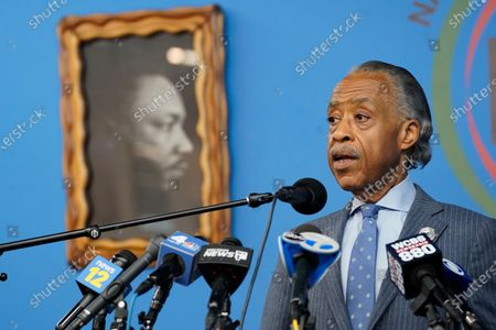 Rev. Al Sharpton is framed by a portrait of Martin Luther King Jr. as he speaks to reporters about the legacy of former New York City Mayor David Dinkins, during a news conference at the National Action Network headquarters in New York. Dinkins, New York City's first African-American mayor, died Monday, Nov. 23, 2020. He was 93