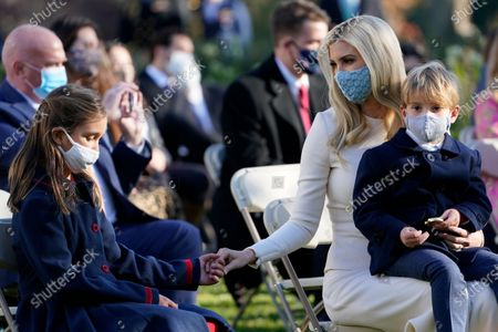 Ivanka Trump, Assistant to the President, sits with her son Theodore Kushner, and reaches out to her daughter Arabella Kushner, left, as they wait for President Donald Trump to pardon Corn, the national Thanksgiving turkey, in the Rose Garden of the White House, in Washington