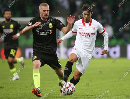 Sevilla's Oliver Torres, left, vies for the ball with Krasnodar's Yury Gazinsky during the UEFA Champions League, group E, soccer match, between Krasnodar and Sevilla at the Krasnodar Stadium in Krasnodar, Russia