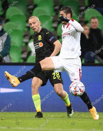 Krasnodar's Igor Smolnikov, left, vies for the ball with Sevilla's Sergio Escudero during the UEFA Champions League, group E, soccer match, between Krasnodar and Sevilla at the Krasnodar Stadium in Krasnodar, Russia